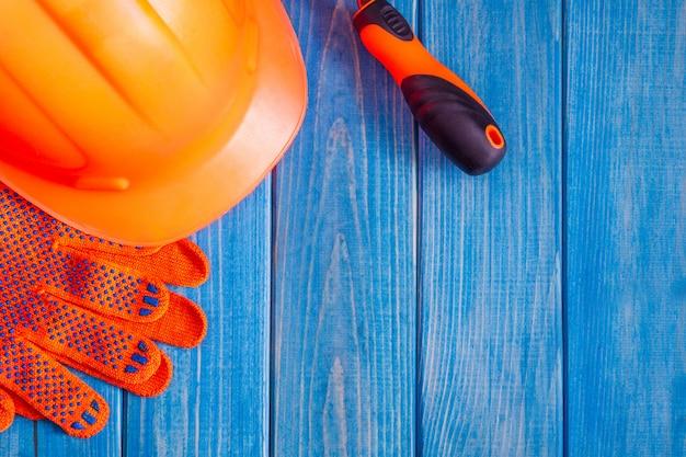 Orange schutzhelm und werkzeug auf hölzernen vintage blauen brettern