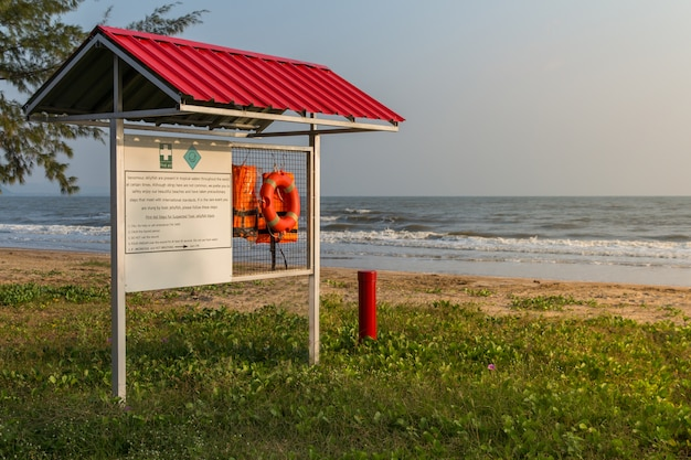 Orange schwimmwesten, die an einem gestell mit warnschild für erste hilfe auf strandhintergrund hängen