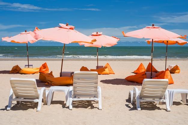 Orange sitzsack unter orange sonnenschirm und bettstuhl am strand im sommer in cha-am