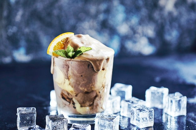 Orange soda creamsicle ice cream float in glas, dekoriert mit einem stück orange, strohhalmen und blättern auf minze, umgeben von eiswürfeln