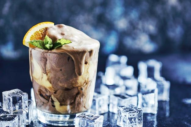 Orange soda creamsicle ice cream float in glas mit orangenstück, strohhalmen und blättern auf minze verziert, umgeben von eiswürfeln auf steintisch