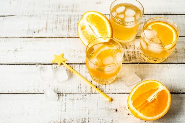 Orange sommergetränk mit eis in den gläsern, flasche, frische orangen auf weißem hintergrund. horizontales bild