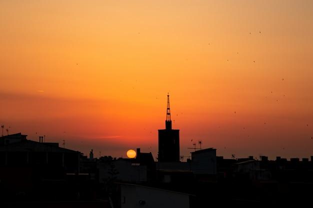 Orange sommersonnenaufgang, draufsicht des dachs eines alten kirchturms über der stadt.