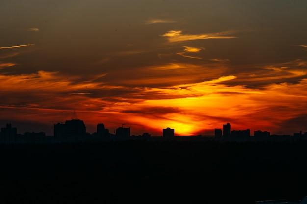 Orange sonnenuntergang über der stadt bedeckt durch wolken über minsk, weißrussland.