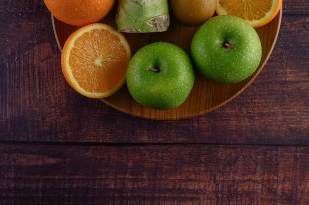 Orange stücke, apfel, kiwi und brokkoli auf einer hölzernen platte.