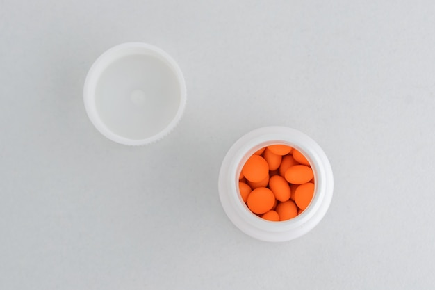 Orange tabletten in einer plastikflasche auf einem weißen hintergrund, der bo