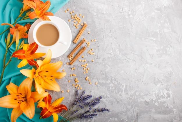 Orange taglilie und lavendelblüten und eine tasse kaffee auf grauem betonhintergrund, mit blauem textil. draufsicht.