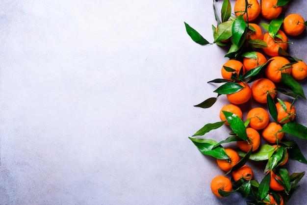 Orange tangerinen (orangen, mandarinen, clementinen, zitrusfrüchte) mit grünen blättern auf licht, kopienraum. mit textfreiraum für ihren text