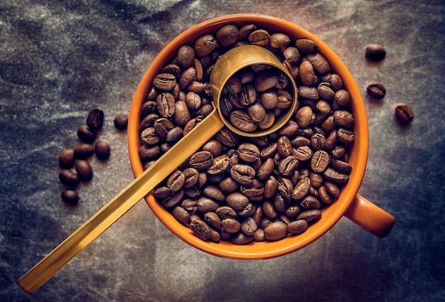 Orange tasse gefüllt mit gerösteten kaffeebohnen mit messlöffel, vintage-stil. geringe schärfentiefe