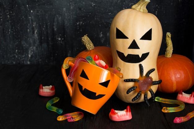 Orange tasse mit süßigkeiten für halloween und gemalter kürbis auf dem schwarzen hintergrund