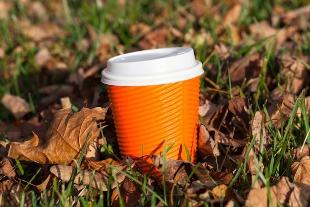Orange tassen liegen im gras und im gelben herbstlaub