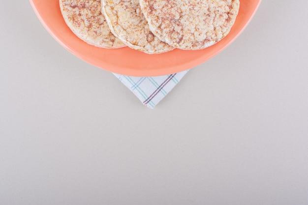 Orange teller mit köstlichen reiskuchen auf weißem tisch. foto in hoher qualität