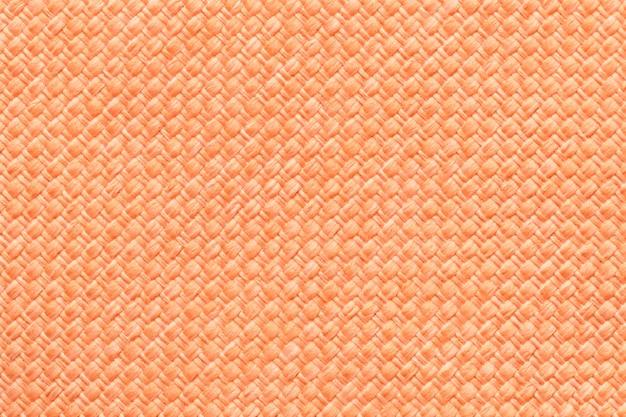 Orange textilhintergrund mit kariertem muster, nahaufnahme. struktur des gewebemakros.
