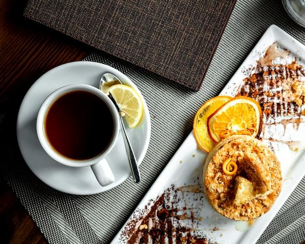 Orange torte und eine tasse schwarzen tee mit zitronenscheibe