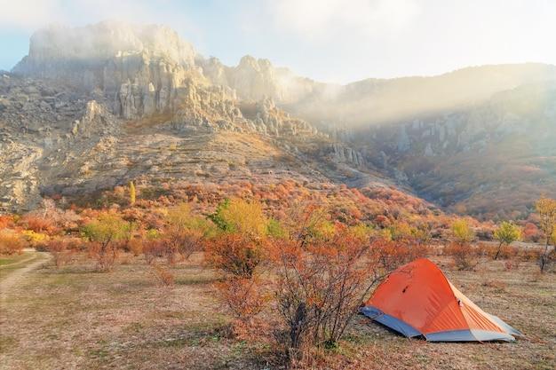 Orange touristenzelt auf dem felsigen berggebiet beleuchtet durch die strahlen der morgensonne, das konzept des tourismus oder des urlaubs
