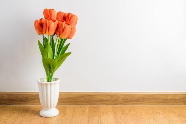 Orange tulpe blüht blumenstrauß im vase auf bretterboden vor zementwand