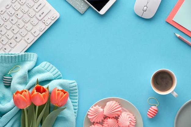 Orange tulpen auf minze färbten baumwollstrickjacke, grußkarten und umschläge, tastatur, handy, platte des eibisches und kaffee