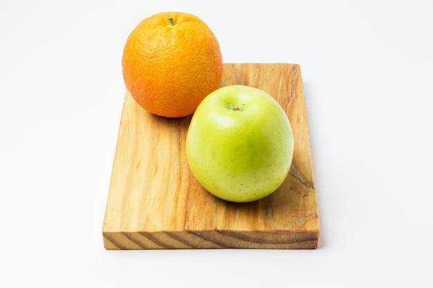 Orange und apfel auf einem holzbrett