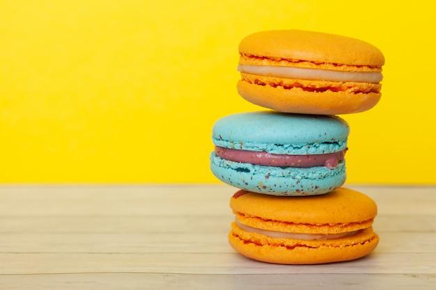 Orange und blaue makronen, französische plätzchen als festlichkeit für den feiertag
