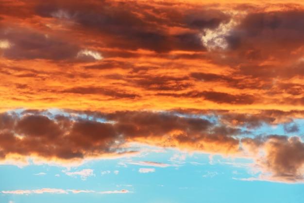 Orange und blauer dramatischer himmel mit wolken bei sonnenuntergang