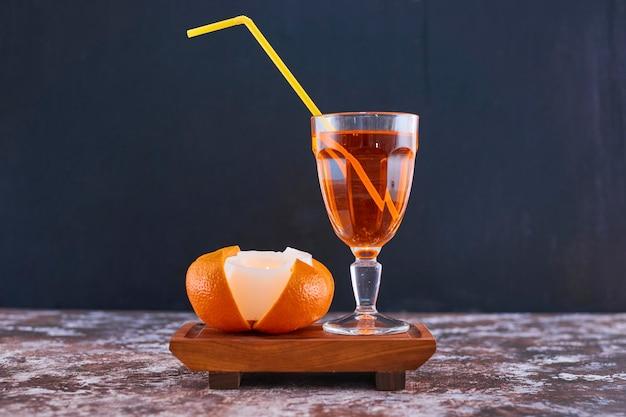 Orange und ein glas saft mit gelber pfeife auf holzplatte auf dem marmor in der mitte. hochwertiges foto