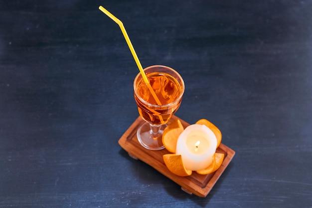 Orange und ein glas saft mit gelber pfeife auf holzplatte, winkelansicht