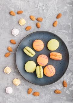 Orange und grüne macarons oder macaroons-kuchen auf blauer keramikplatte auf einer grauen betonoberfläche. draufsicht.