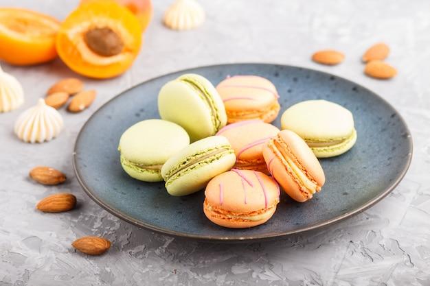 Orange und grüne macarons oder macaroons-kuchen auf blauer keramikplatte auf einer grauen betonoberfläche. seitenansicht, selektiver fokus.