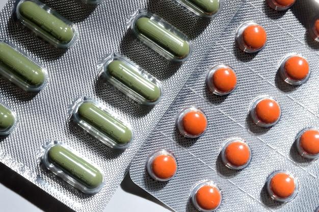 Orange und grüne pillen in einer folienblase