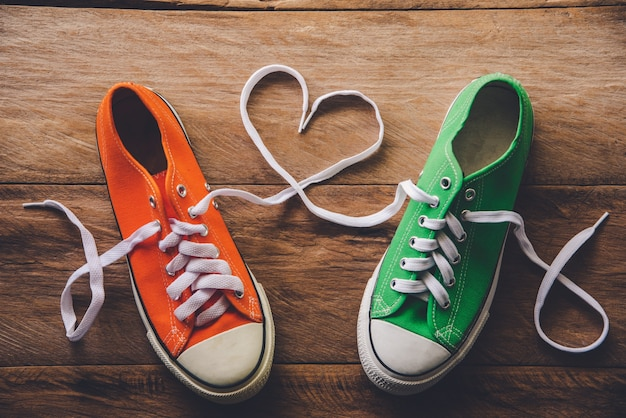 Orange und grüne turnschuhe mit einem seil im herzstil. -valentine's day liebeskonzept