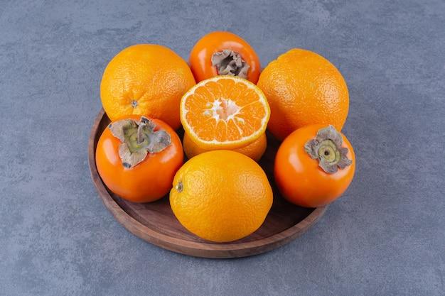 Orange und kaki auf holzplatte auf marmortisch.