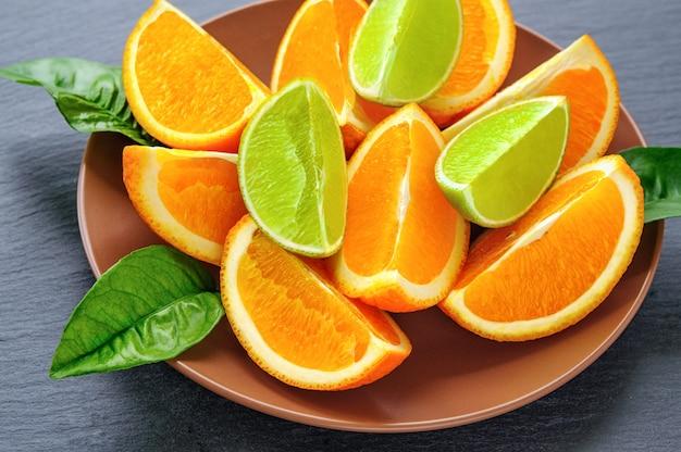 Orange und kalk geschnittene segmente mit grünen blättern auf brauner platte