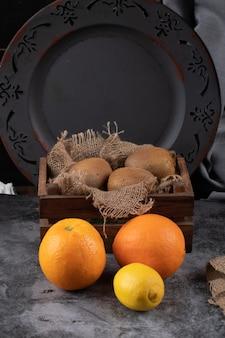 Orange und kiwies in einem dunklen rustikalen hintergrund