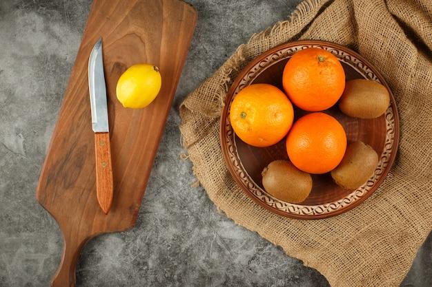 Orange und kiwies in einer keramikschale. ein messer und eine zitrone.