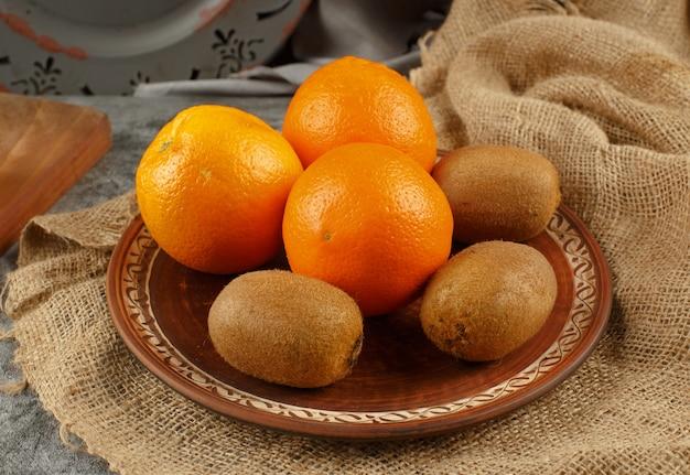 Orange und kiwies in einer keramikschale.