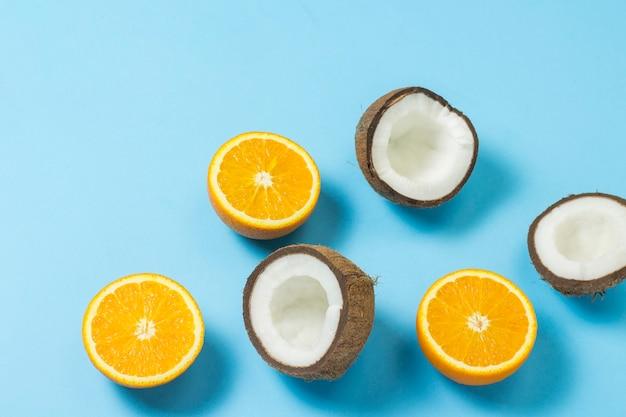 Orange und kokosnuss auf eine blaue fläche schneiden.