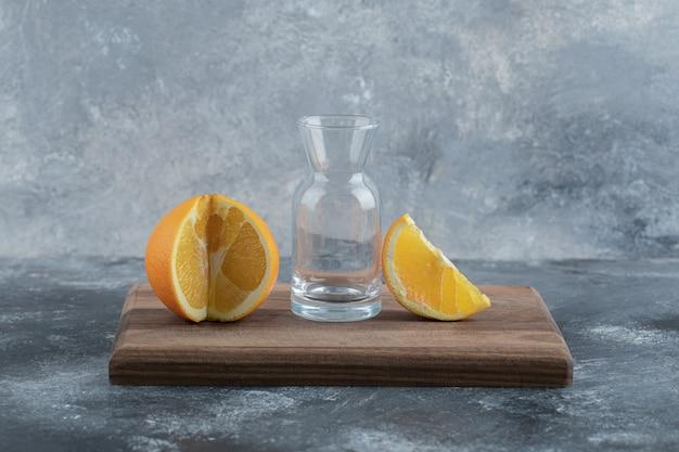 Orange und leeres glas auf holzbrett.