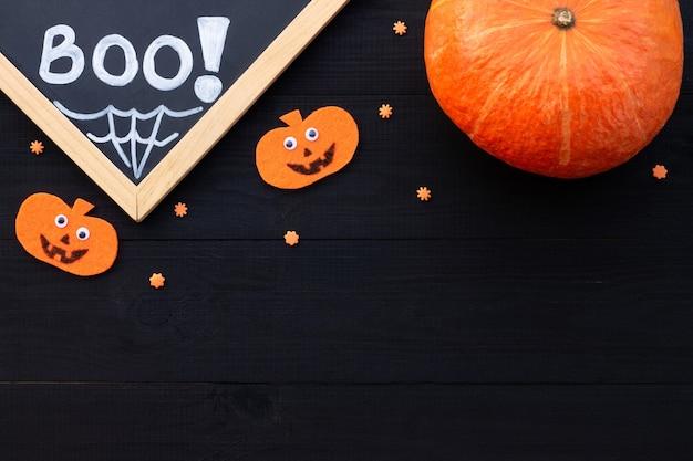 Orange und schwarzes halloween-flatlay. kreideaufschrift boo, kürbisse aus filz auf schwarzem holzhintergrund. platz kopieren.