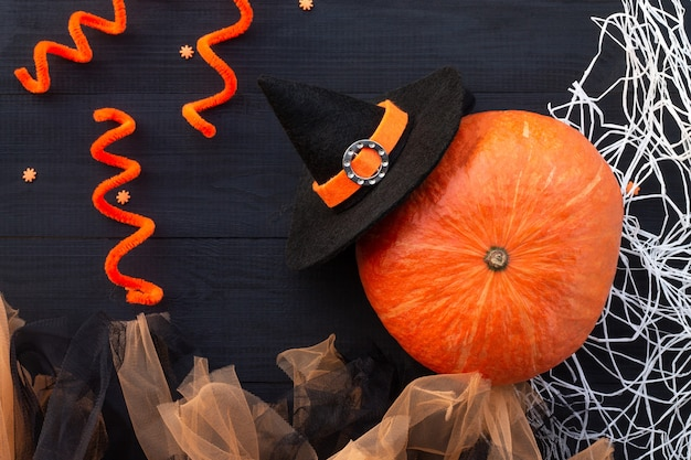 Orange und schwarzes halloween-flatlay. kürbis, tüll, hexenhut, weißes spinnennetz auf schwarzem holzhintergrund