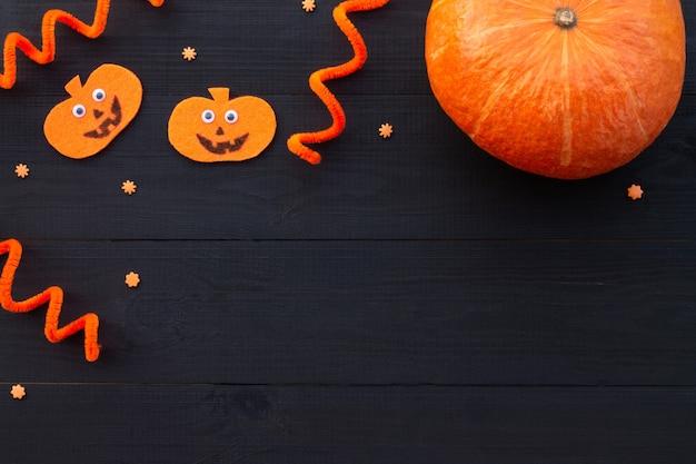 Orange und schwarzes halloween-flatlay. kürbisse aus filz und echtem kürbis auf schwarzem holzhintergrund. platz kopieren.
