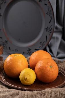 Orange und zitrone mit einer dunklen platte dahinter.