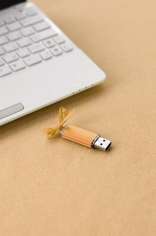 Orange usb-flash-speicherkarte mit einem bogen liegt neben einem weißen laptop auf einer decke aus weichem und pelzigem hellorangeem fleece-stoff.