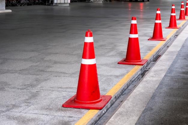 Orange verkehrskegel oder -trichter, die eine reihe am parken stehen