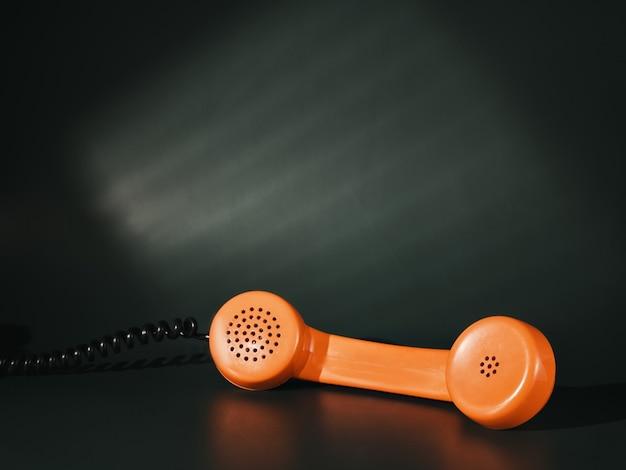 Orange vintage telefonhörer auf grünem hintergrund