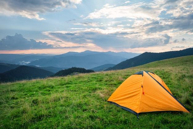 Orange zelt auf grünem gras in den bergen im sommer
