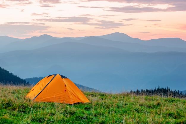 Orange zelt auf wiese in den bergen unter rosa himmel