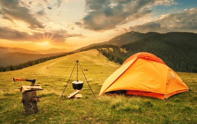 Orange zelt mit einem vorbereiteten lagerfeuer bei sonnenuntergang
