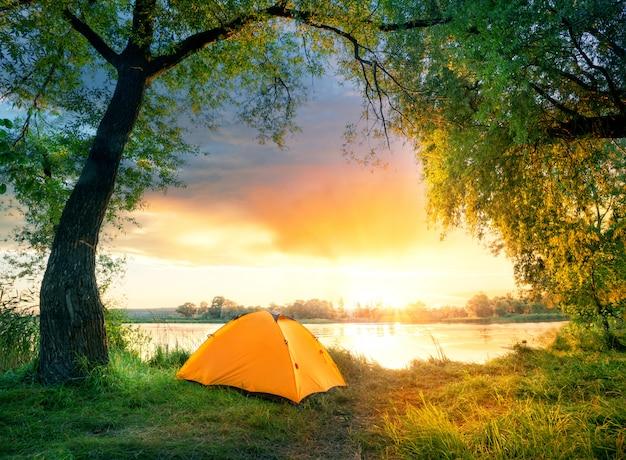 Orange zelt umgeben von grünen blättern durch fluss