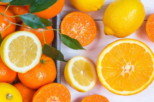 Orange, zitrone, flaches draufsichtmuster der zitrusfrüchte auf weißem hölzernem hintergrund