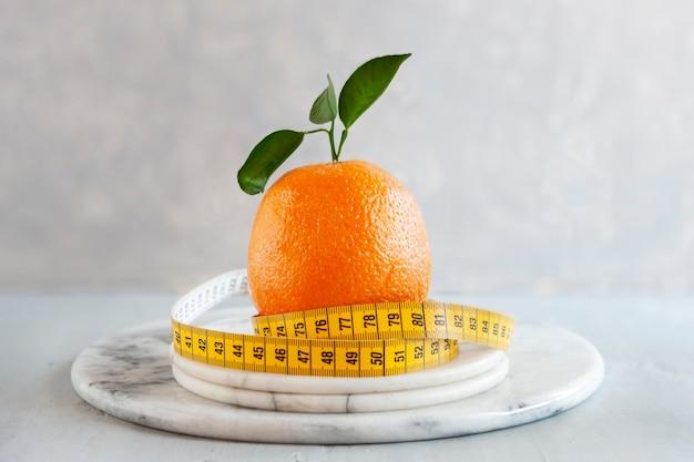 Orange zitrusfrucht und zentimeter. frisches obst, konzept zur gewichtsreduktion, diät, ketogene diät, intermittierendes fasten
